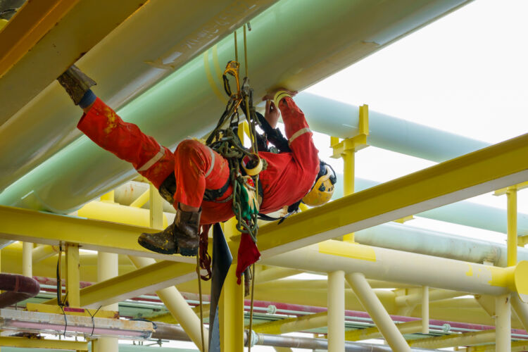 working,at,height.,a,group,of,abseilers,wearing,red,coverall
